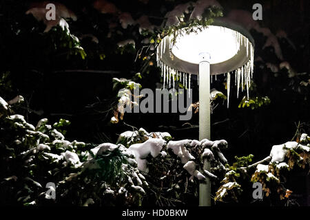 street light at night covered with snow and icicles. - Stock Photo