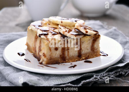 Cheese cake with chocolate syrup and piece of banana - Stock Photo