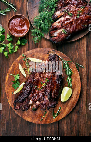 Barbecue pork ribs on wooden board, top view - Stock Photo