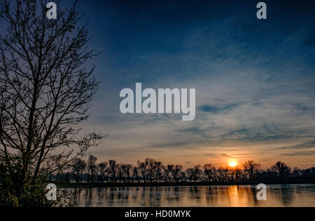 Beautiful winter sunset as seen over a lake at a nature reserve showing the long tree line in the distance. - Stock Photo