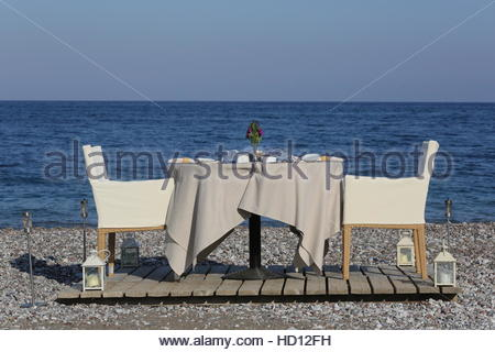 Romantic dinner table set for two in a private tent by the beach on ...