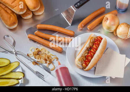 Preparing hot dogs in the stainless steel kitchen of a food truck or hot dog stand. - Stock Photo