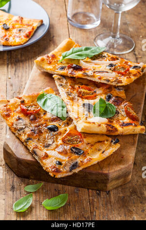 Fresh baked homemade pizza slices served on wooden table. - Stock Photo