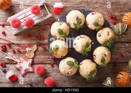 Freshly baked muffins with cranberries close-up on the table. horizontal view from above - Stock Photo