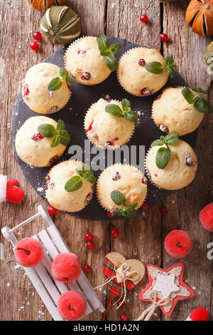 cranberry muffins with mint and Christmas decoration close-up on the table. vertical view from above - Stock Photo