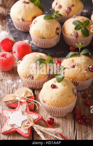 Freshly baked muffins with cranberries close-up on the table. Vertical - Stock Photo