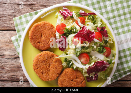 Dietary carrot burgers and fresh salad mix close-up on a plate. Horizontal view from above - Stock Photo