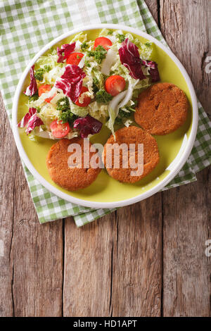 Dietary carrot cutlets and salad of chicory, cabbage and tomatoes close-up on a plate.  vertical view from above - Stock Photo