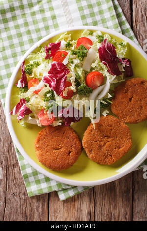 Dietary carrot burgers and fresh salad mix close-up on a plate. vertical view from above - Stock Photo