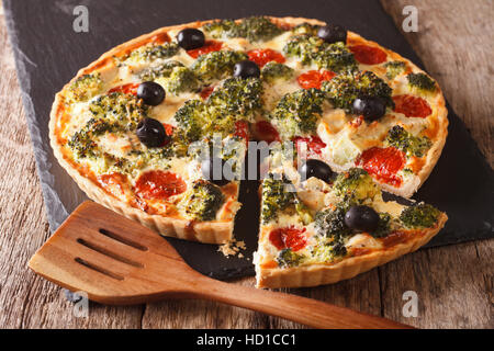 savory tart with chicken, broccoli, tomatoes and olives close-up on the table. horizontal - Stock Photo