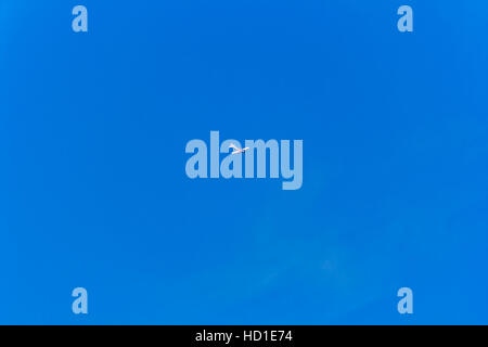 Photo of flying military plane in blue sky - Stock Photo