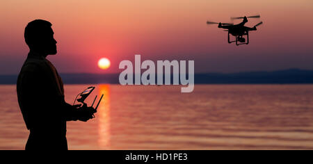 Man flying a drone near seaside at the sunset. - Stock Photo