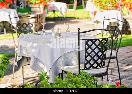 Typical restaurant terrace with chairs and tables ready for a meal at the luxurious resort in Ascona on Lake Maggiore - Stock Photo