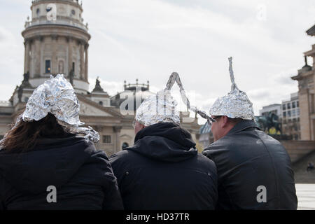 Global march against Geoengineering. Berlin, Germany. Three people with tinfoil  hats mock the protesters. - Stock Photo