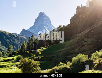 Matterhorn mountain and green hill in Zermatt, in Switzerland in summer. With special rays of light and sun flare - Stock Photo
