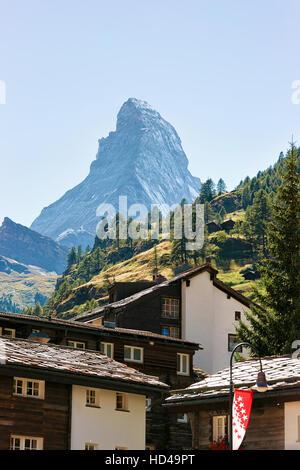 Chalets of resort city Zermatt with Matterhorn mountain in Switzerland in summer. With flag of Valais - Stock Photo