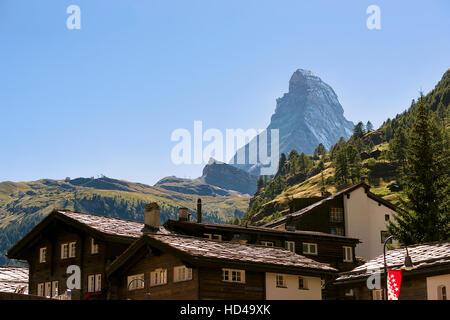 Chalets of resort city Zermatt with Matterhorn mountain, Switzerland in summer. With flag of Valais - Stock Photo