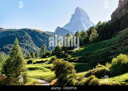 Panoramic view of Matterhorn mountain and green valley with traditional Swiss chalets, Zermatt, Switzerland in summer. - Stock Photo