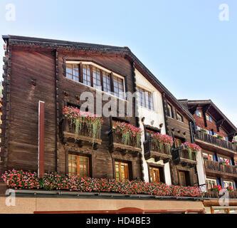 Zermatt, Switzerland - August 24, 2016: Traditional Swiss chalets with flowers on balconies in resort city Zermatt - Stock Photo