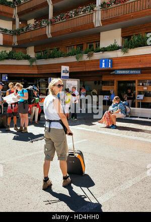Zermatt, Switzerland - August 24, 2016: Young woman with luggage at the tourist office of Zermatt in Switzerland. - Stock Photo