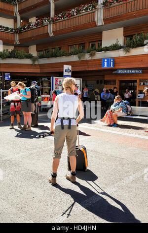 Zermatt, Switzerland - August 24, 2016: Young woman with luggage at the tourist office in Zermatt in Switzerland. - Stock Photo