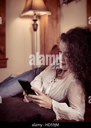 Young woman lying on a sofa at home using Apple iPhone 7 Plus smartphone - Stock Photo