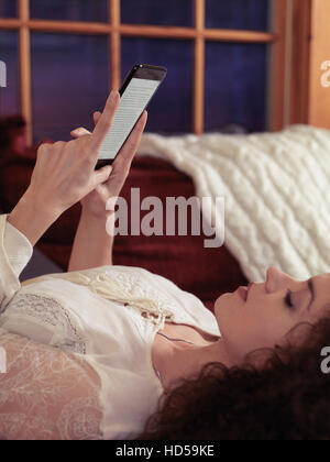 Woman reading book on iPhone 7 Plus at home lying on a sofa - Stock Photo