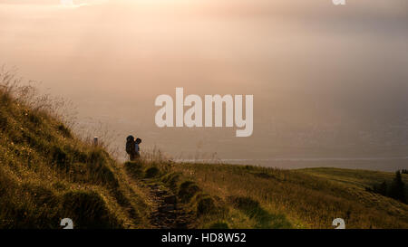 An exhausted, unrecognisable hiker with a large backpack looking into the golden hour - Stock Photo