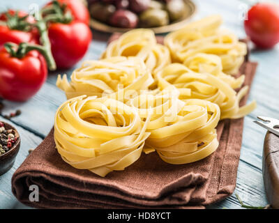 Pasta ingredients. Cherry-tomatoes, spaghetti pasta and spices on the wooden table. - Stock Photo