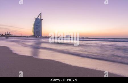 Luxury hotel Burj Al Arab on the coast of Persian Gulf after sunset. Dubai, UAE. - Stock Photo