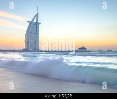 Luxury hotel Burj Al Arab on the coast of Persian Gulf after sunset. Dubai, UAE. - Stock Photo