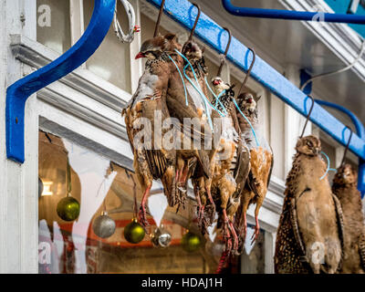 Malton, UK. 10th December, 2016. Game birds, pheasant, partridge and grouse, hanging outside traditional butchers - Stock Photo