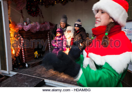 Toronto, Canada. 9th December, 2016. Christmas Market Elf gestures while family is photographed with Santa behind - Stock Photo