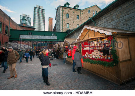 Toronto, Canada. 9th December, 2016. Girl in awe of Xmas decoration booth at Christmas Market, Gooderham Worts sign - Stock Photo