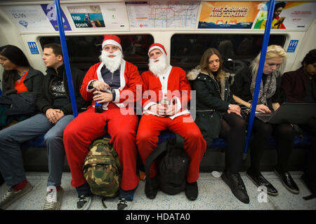 SantaCon, London, UK 10th December 2016 Two men dressed as Santas travel by London Underground for SantaCon, London, - Stock Photo