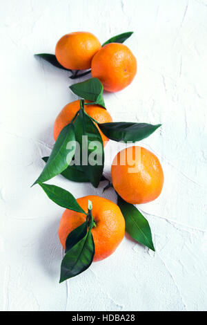 Tangerines (oranges, mandarins, clementines, citrus fruits) with leaves over rustic white stone background with - Stock Photo