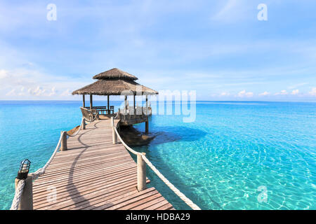 Beautiful tropical beach landscape with wooden pier and transparent turquoise sea water, paradise travel vacation - Stock Photo