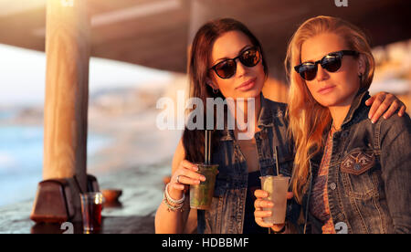 Portrait of a two beautiful girls spending leisure time in the outdoor cafe with drinks, models wearing stylish - Stock Photo