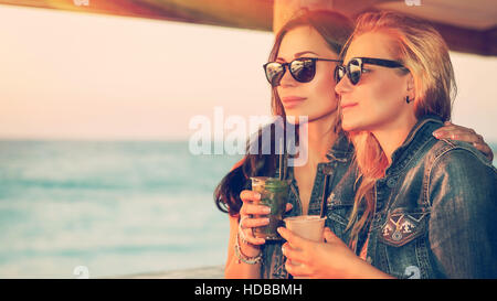 Portrait of a two beautiful girls spending leisure time in the outdoor cafe, drinking tasty cocktails and enjoying - Stock Photo
