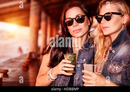 Two gorgeous women with refreshing drinks having fun in the beach cafe, wearing stylish sunglasses and enjoying - Stock Photo
