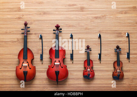 Set of four toy string musical orchestra instruments: violin, cello, contrabass, viola on a wooden background. Quartet. Music concept.