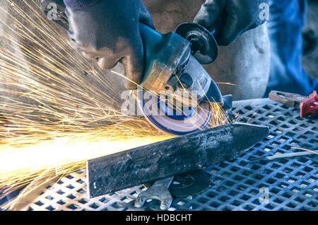 Mechanical worker welding a piece of metal - Man workinng in aofficine with welding machine - Stock Photo