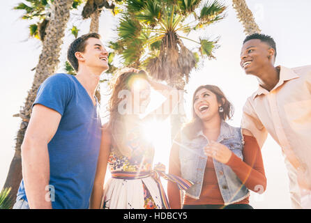 Four young people having fun and laughing outdoors - Multiethnic group of friends gathering on the beach at sunset - Stock Photo