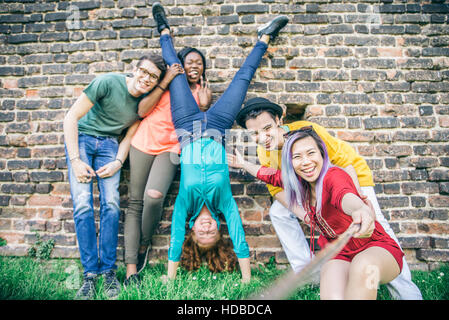 Group of cheerful young people taking a self portrait and having fun outdoors - Happy teens photographing themselves - Stock Photo