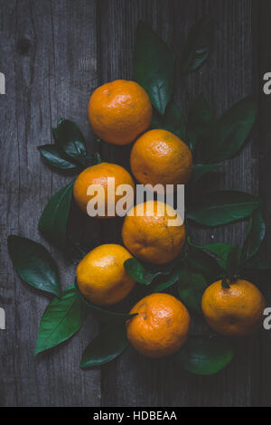 Fresh tangerines with green leaves on rustic wooden table. Top view, vertical composition, toned image. - Stock Photo