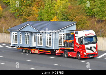 Part of factory assembled prefabricated park home lodge being transported on UK motorway on hgv low loader articulated - Stock Photo