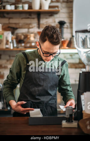 Male waiter prepares the check in coffee house. Coffee house, restaurant or bars concept. - Stock Photo