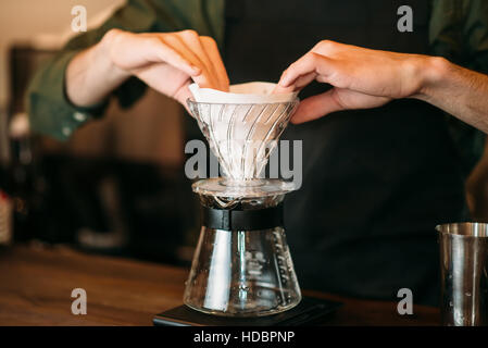Closeup of male hands  prepares coffee pot standing on bar counter. - Stock Photo