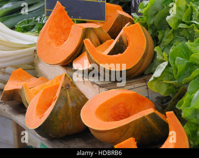 Pieces of fresh sliced pumpkin displayed in a farmers market. - Stock Photo