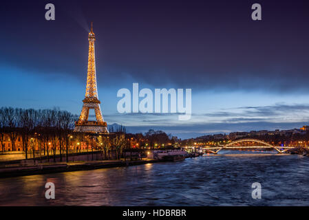 The Eiffel Tower illuminated at twilight with banks of the Seine River and the Debilly Footbridge. Paris, France - Stock Photo